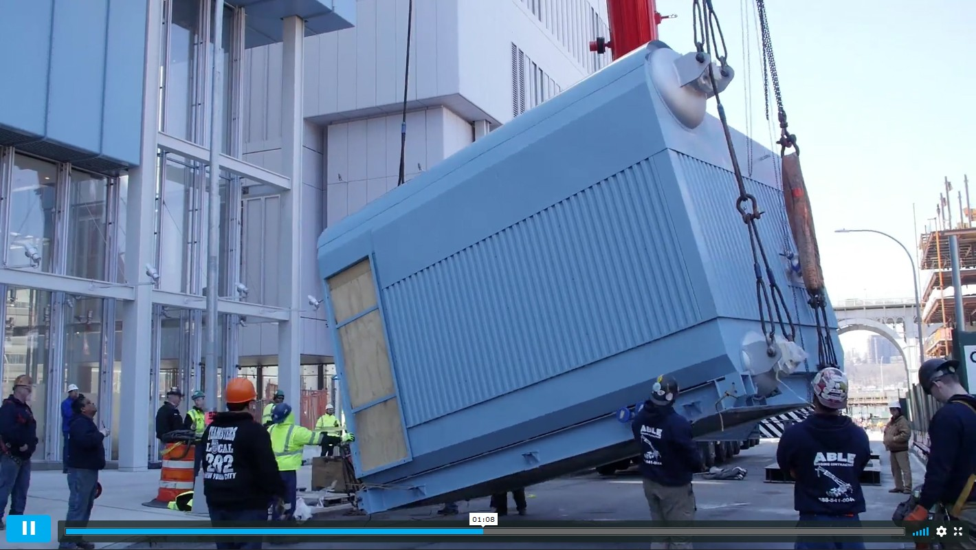 Screenshot of video detailing the Central Energy Plant's boiler installation, showing the equipment being hoisted from the ground, surrounded by workers.