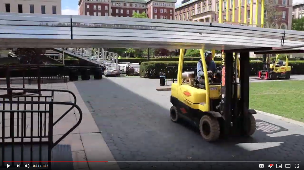A screenshot of the video Building Commencement, showing a forklift carrying bleachers