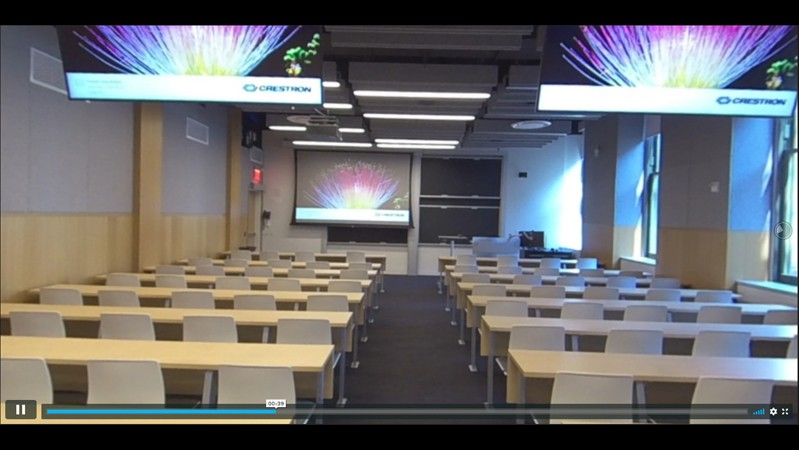 A screenshot of the 360-degree video of the accessible spaces in Chandler Hall, with rows of tables and chairs, two screens overhead, and a projector screen pulled down against the wall.