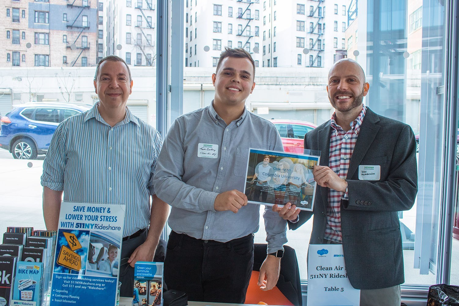 Three men standing in front of a Clean Air NY table with lots of pamplets on it, with one giving a Clean Air NY certificate to Daniel Allalemdjian, director of transportation management at Environmental Stewardship