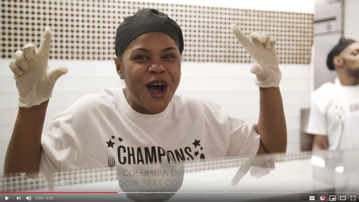 A still of a video on Columbia Dining winning the Daily Meal award, with a Columbia Dining employee exciting and holding up #1 sign with her hands