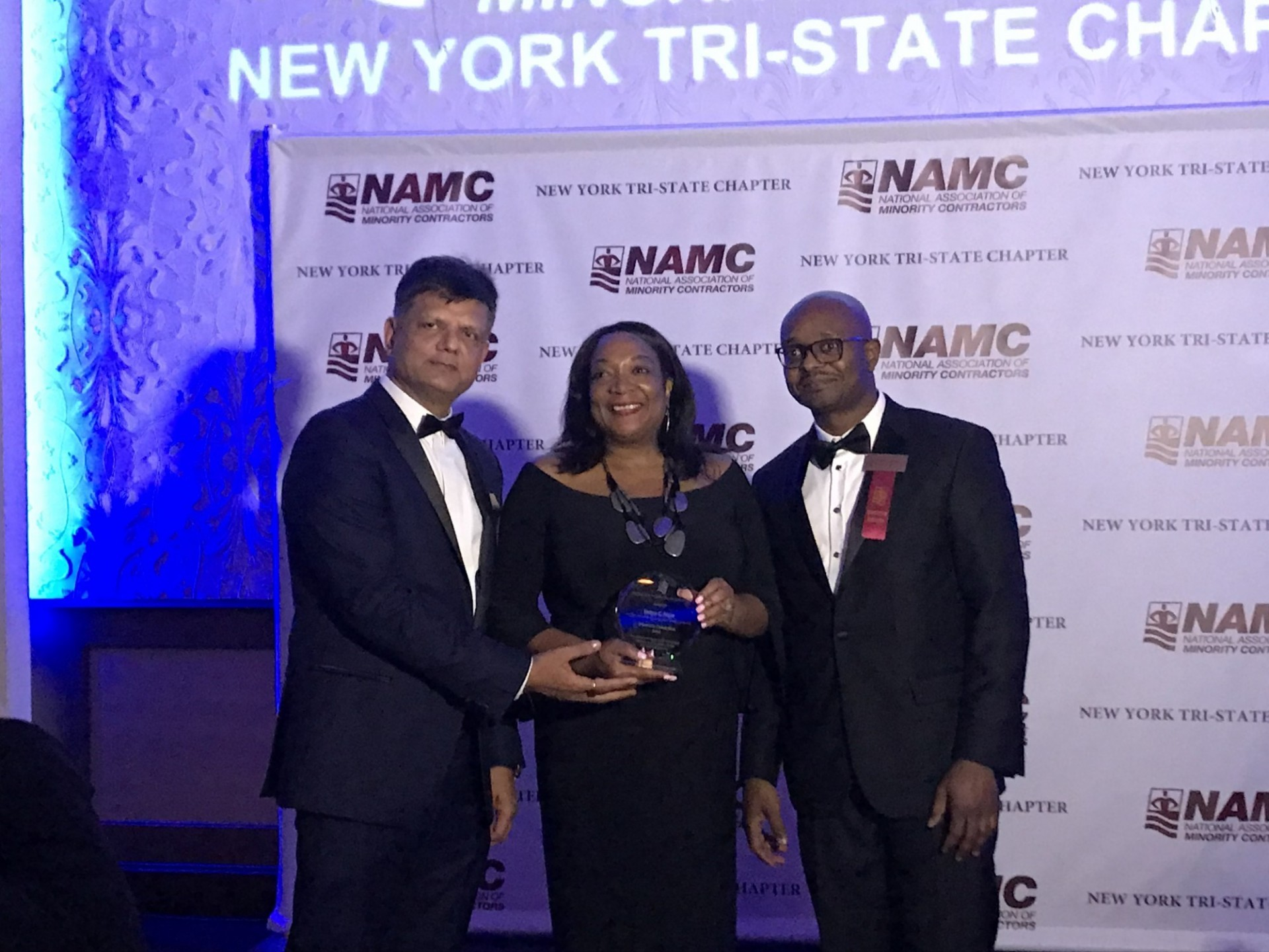 Tanya Pope (center) accepting the Diversity Champion Award from NAMC-NY President Nayan Parikh (left) and Andrew Fisher, an executive member of the organization.