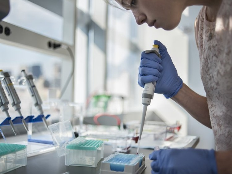 A woman with blue gloves in a lab, using a syringe
