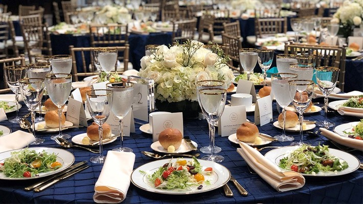 A place setting with food, flowers, on a table with a dark blue table cloth